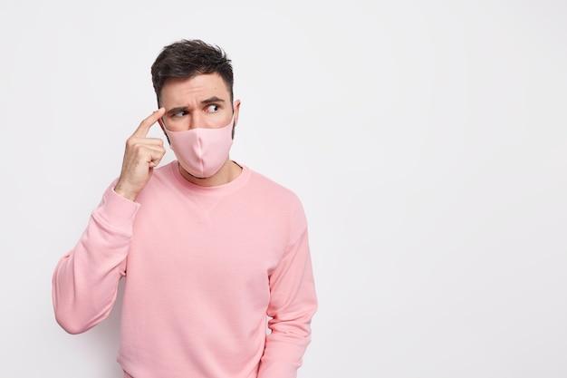 Covid19ウイルスとヘルスケアの概念。真面目な男は、コロナウイルスの検疫中に真面目な表情で保護マスクを着用して寺院に指を集中させます