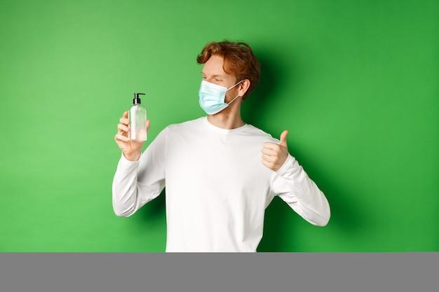Covid-19, вирус и концепция социального дистанцирования. красивый молодой человек с рыжими волосами, в медицинской маске, глядя на антисептик и показывая большой палец вверх, зеленый фон.