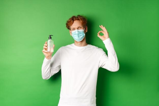 Covid-19、ウイルスと社会的距離の概念。赤い髪の若い男を笑顔、コロナウイルスのフェイスマスクを身に着けて、大丈夫な兆候と手指消毒剤、緑の背景を示しています。