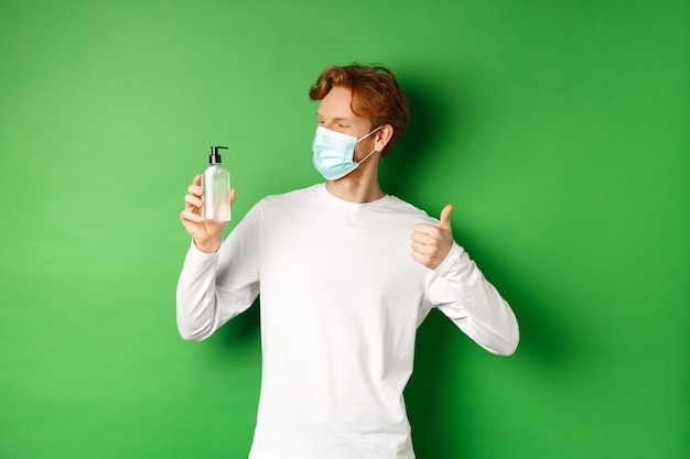 Covid-19, virus and social distancing concept. handsome young man with red hair, wearing medical mask, looking at antiseptic and showing thumb-up, green wall
