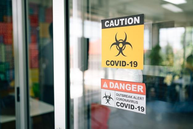 Covid-19 경고 표지판이 유리문에 붙어 있습니다. 코로나 바이러스의 검역 및 발생 경보 징후.
