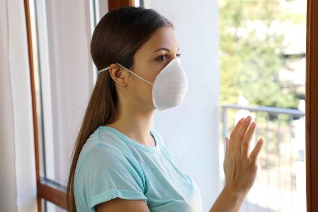 Covid-19フェイスマスク保護を身に着けている女性の家の隔離の自動検疫