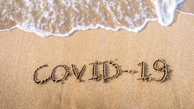 波が来る海岸の砂浜に書かれたcovid-19