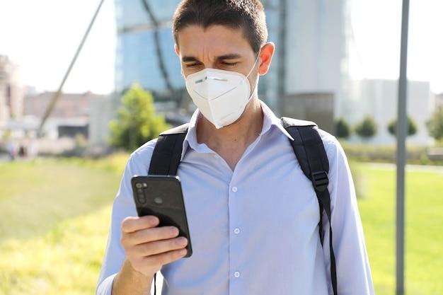 Covid-19現代の街でスマートフォンアプリを使用してkn95保護マスクを身に着けている若いビジネスマン