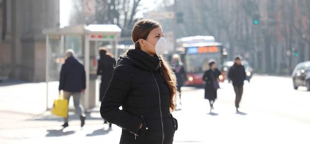 Covid-19 молодая женщина на городской улице в защитной маске для защиты от коронавирусной болезни 2019.