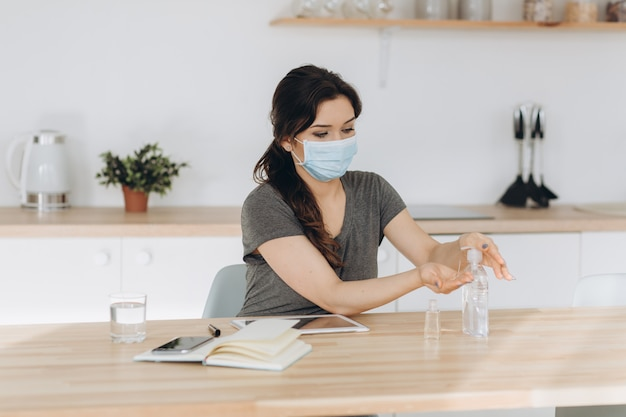 Covid-19 young woman using wash hand sanitizer gel dispenser, against novel coronavirus (2019-ncov) at home. home isolation, auto quarantine, antiseptic, hygiene and healthcare concept.