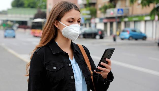 Covid-19 молодая женщина в маске ffp2 использует смартфон на городской улице