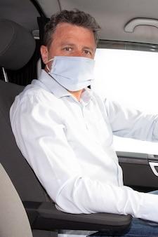 コロナウイルスcovid-19検疫中に車を運転している医療用マスクを着ている青い目をした男