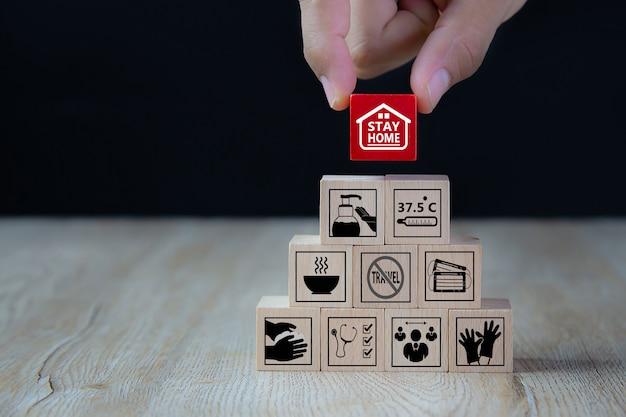 家にいて、木のおもちゃブロックのcovid-19アイコン。コロナウイルス感染の健康と医療保護の概念。
