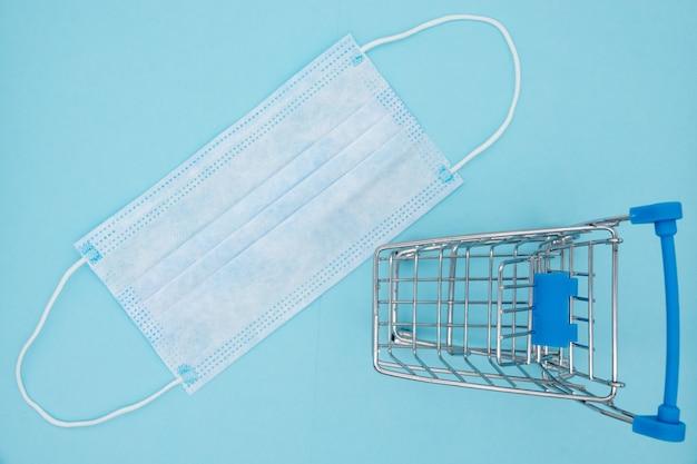 Маска и тележка на синем фоне, покупки для защиты covid-19.