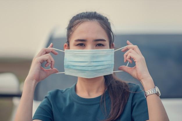 アジアの女性はフェイスマスクまたはサージカルマスクを使用してコロナウイルスまたはcovid 19を保護し、家に安全に滞在するために家にいます