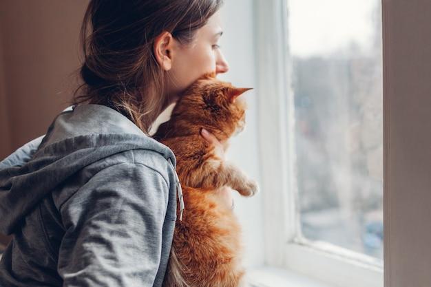 コロナウイルスcovid-19パンデミック時の自宅での分離。猫とウィンドウを見ている女性。