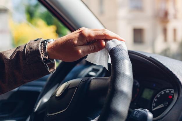 コロナウイルス車の消毒。男はウェット抗菌アルコールワイプでホイールをきれいにします。 covid-19パンデミック