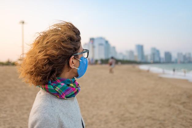 ニャチャンビーチ、ベトナムの有名な旅行の決定で屋外の衛生マスクを身に着けている白人女性。アジアの新しいコロナウイルスcovid-19のリスクに対する医療マスク保護の観光客
