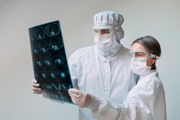 Врачи, стоящие на белом фоне, осматривают рентгеновский снимок пневмонии пациента covid-19 в клинике. коронавирусная концепция.