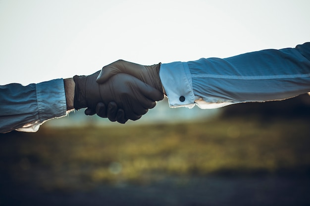 黒いラテックスまたはゴム手袋を着用して同僚として一緒に手を繋いでいる医師。コロナウイルスまたはcovid-19保護の概念。