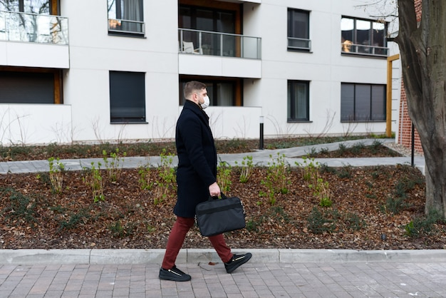 Молодой красивый мужчина гуляет в жилом районе во время глобальной пандемии коронавируса covid-19, в карантине с хирургической маской