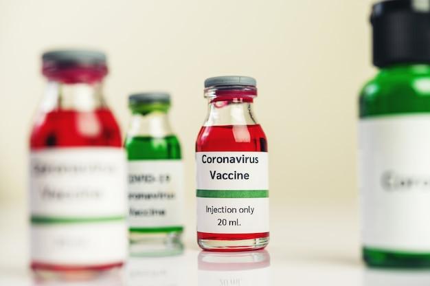 Covid-19に対するワクチンは、床に置かれたボトルの中に赤と緑が入っています。