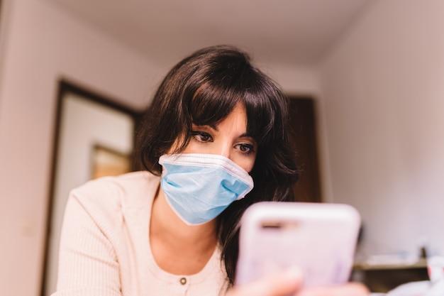 携帯電話を使用して彼女の顔に医療用呼吸マスクを呼吸している自宅の女性。パンデミックコロナウイルス、ウイルスcovid-19。隔離、感染防止のコンセプト。彼女の顔に焦点を当てます。
