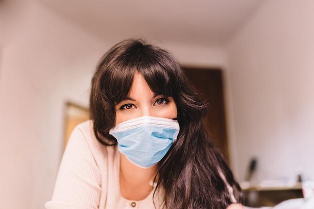 強い視線で笑っている彼女の顔に呼吸用呼吸マスクを着用している自宅の女性。パンデミックコロナウイルス、ウイルスcovid-19。隔離、感染防止のコンセプト。