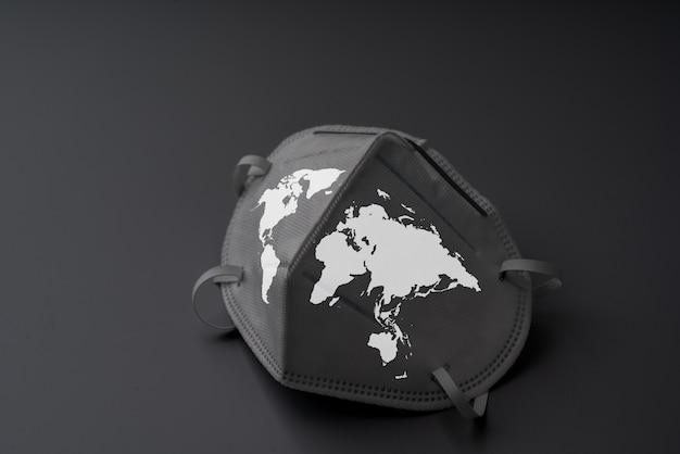 流行の概念とcovid 19ウイルスの世界地図アイコンが付いた手術マスク