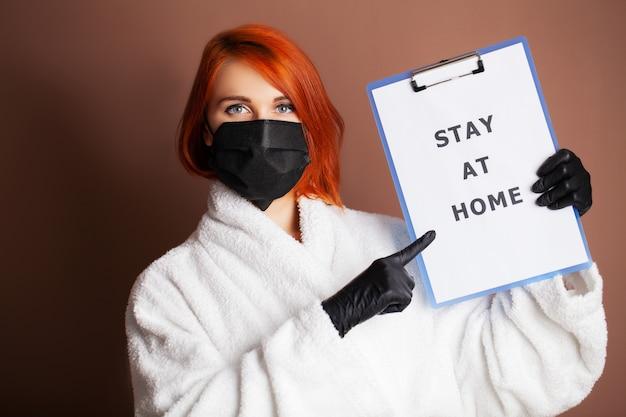 碑文と空白を保持している女性はcovid-19の拡散をやめるように呼びかけ家にいます