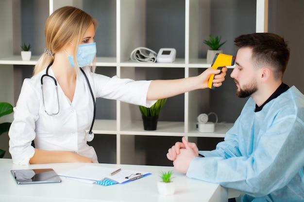 医師は、流行病のcovid-19中に患者の体温を測定します。