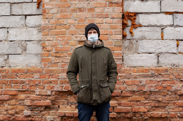 Молодой парень в медицинской маске возле заброшенного здания. респираторные вирусные заболевания covid-19 корь грипп ветряная оспа.