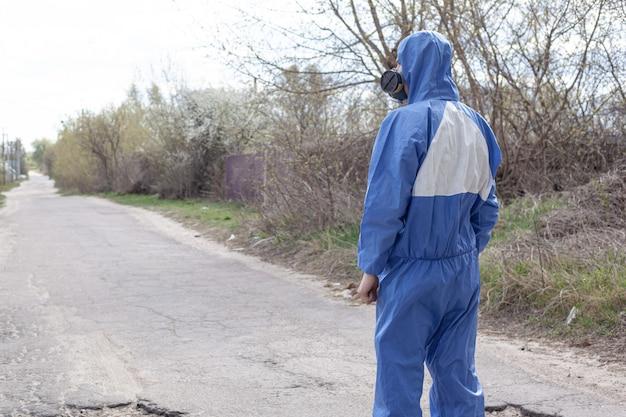 青い保護服と防毒マスクをかぶった男が背を向けて道に立っています。検疫パンデミック発生covid-19。