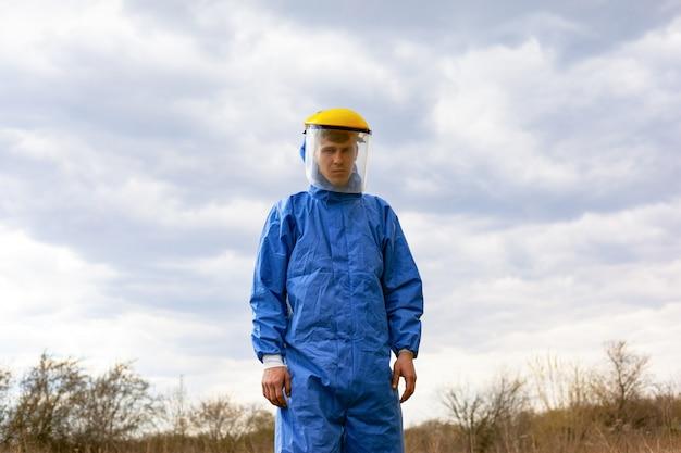 青い保護服とプラスチック製の医療用マスクの男。 covid-19に対する保護のためのフォーム。検疫、パンデミックコロナウイルス