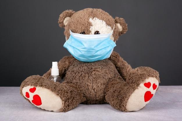 暗い背景に防腐剤と青い医療マスクに身を包んだ茶色のテディベアの肖像画。分離記号、検疫、covid-19、家にいる、クローズアップ