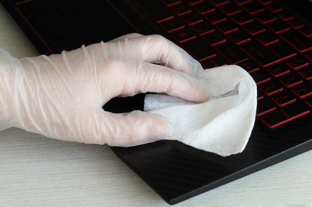 Вирусная очистка и дезинфекция вашего рабочего места. женщина вытирает клавиатуру компьютера дезинфицирующим средством для защиты от коронавируса. остановить распространение коронавируса covid-19.