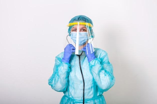 医師、看護師は、分離された白い背景を持つcovid-19コロナウイルスとの戦いのための保護スーツの着用方法を示します。