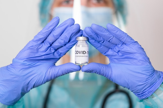 生物学的危険。 covid-19コロナウイルスの流行。防護服、マスク、顔面シールドの医師が注射器とワクチンを保持しています。