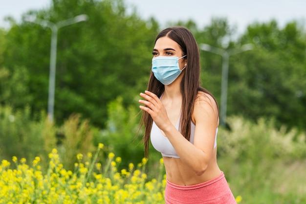 医療用マスク、コロナウイルスパンデミックcovid-19を身に着けているランナー。スポーツ、検疫外科用消毒フェイスマスク保護のアクティブライフ。コロナアウトブレイクの陸上競技トラックの屋外ランニング。