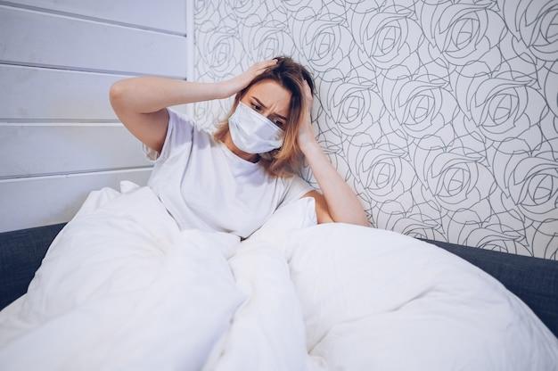 コロナウイルス病(covid-19)の症状は、鼻水、喉の痛み、咳、発熱です。コロナウイルス感染の病気の若い女性。自宅検疫でベッドに横たわっている患者