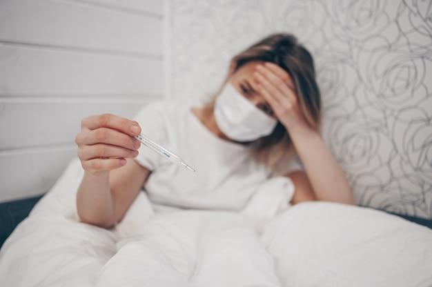 温度計付きベッドで横になっていると自宅検疫隔離で高温をチェックする病気の女性。コロナウイルスcovid-19。感染症は呼吸器疾患の最初の症状、咳、頭痛、発熱を引き起こします