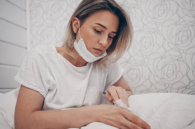 Covid-19による汚染を避けるためにアルコールで綿を使用して拭く手消毒剤によるコロナウイルス分離家庭検疫洗浄中にベッドで横になっている顔の防護マスクの女性
