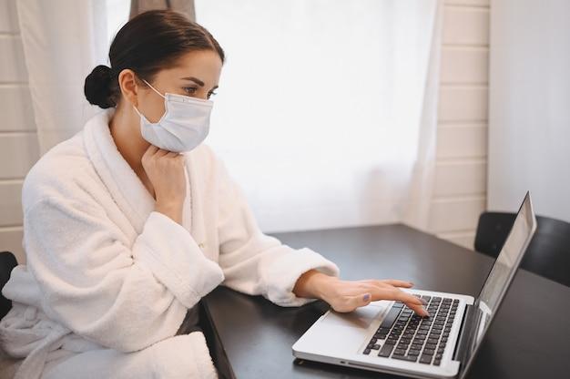 Больной женщине в лицо медицинская маска работает на ноутбуке во время домашнего карантинной изоляции covid-19 пандемического вируса короны. удаленная онлайн работа от дома концепции. симптомы вирусной инфекции коронавируса