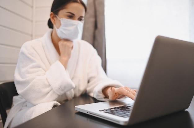 家庭検疫隔離covid-19パンデミックコロナウイルス中にラップトップに取り組んでいる顔医療マスクの病気の女性。ホームコンセプトからのオンライン作業の距離。コロナウイルスのウイルス感染症状