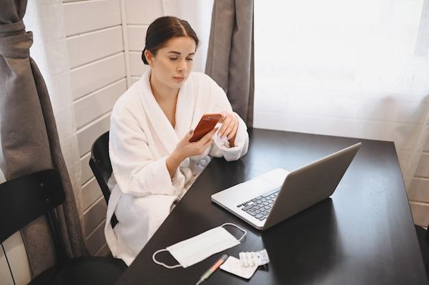 家の検疫隔離中にスマートフォンとラップトップを操作する病気の女性covid-19パンデミックコロナウイルス。ホームコンセプトからの距離の仕事。温度計、薬、テーブルの上の医療マスク