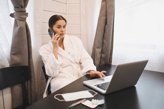病気の女性がスマートフォンを話し、家庭検疫隔離中にノートパソコンで作業しているcovid-19パンデミックコロナウイルス。ホームコンセプトからの距離の仕事。温度計、薬、テーブルの上の医療マスク