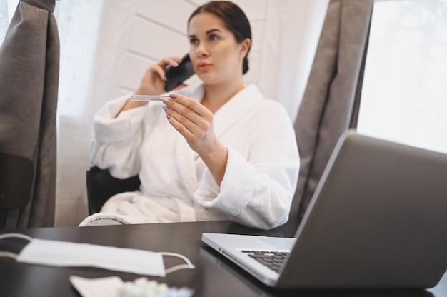 病気の女性がスマートフォンを話し、家庭検疫隔離中にノートパソコンで作業しているcovid-19パンデミックコロナウイルス。ホームコンセプトからの距離の仕事。手、薬、医療用マスクの温度計