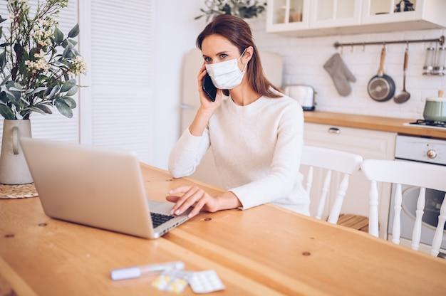 Больная женщина в медицинской маске, говорящая по смартфону и работающая на ноутбуке в домашней кухне во время карантинной изоляции пандемия covid-19