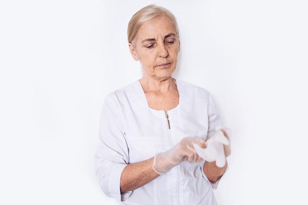 Пожилой старший зрелый женщина-врач или медсестра в белом медицинском халате ставит на перчатки, носить средства индивидуальной защиты изолированы. концепция здравоохранения и медицины. covid-19 пандемический кризис