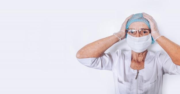 Пожилая уставшая измученная зрелая женщина-врач или медсестра держит голову в белом медицинском халате, перчатках, лицевой маске, надевает средства индивидуальной защиты. здравоохранение и медицина. covid-19 пандемический кризис