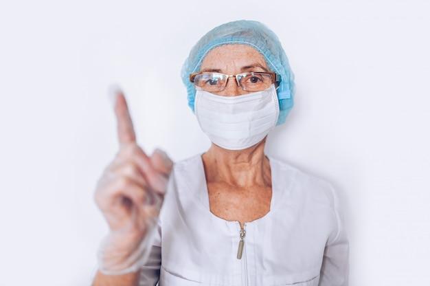 Пожилые пожилые женщины врач или медсестра подняли палец в белом медицинское пальто, перчатки, маска для лица, носить средства индивидуальной защиты изолированы. концепция здравоохранения и медицины. covid-19 пандемический кризис