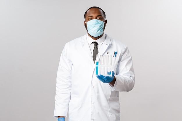 Covid-19, лечение пациентов с коронавирусом и лабораторная концепция. серьезно выглядящий профессиональный афро-американский врач в лицевой маске и латексных перчатках, держа флаконы, пробирки с вакциной