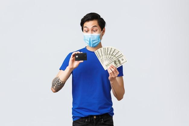 お金、covid-19、簡単な支払い、投資、銀行のコンセプト。クレジットカードを見つめて興奮して驚いたアジア人の男、預金に現金を置き、ドルを持って、医療用マスクに立って