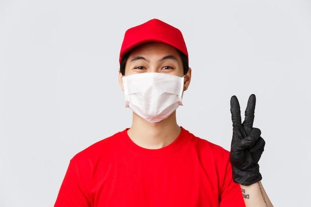 Covid-19、自己検疫オンラインショッピングのコンセプト。アジアの宅配便がポジティブで友好的、医療用マスクと手袋のピースサインを見せ、安全な秩序のための措置が自己検疫に